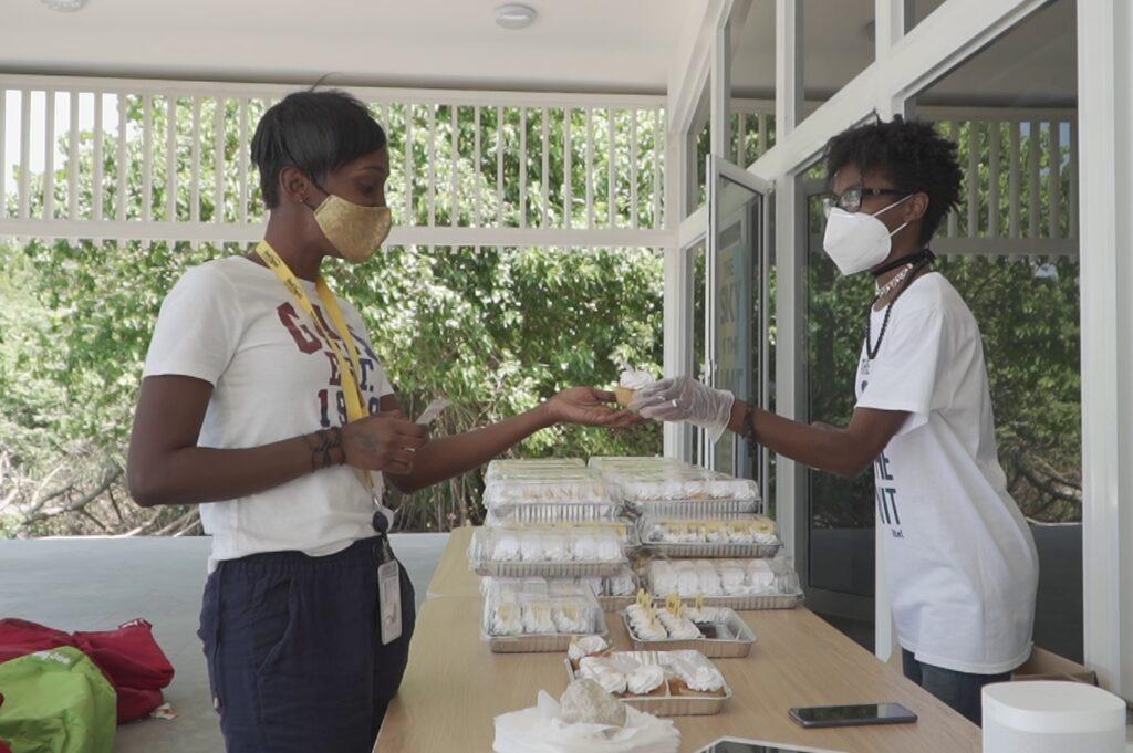itel staff being handed branded cupcakes at itel's brand reveal grab n' go onsite celebration