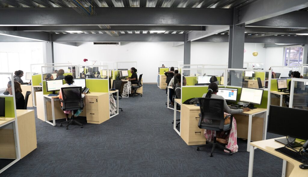 Image featuring itel's Saint Lucia site. The COVID-ready production floor features wide walkway areas between y-shaped desk configurations, with high plexiglass partitions that allow coworkers to communicate safely.
