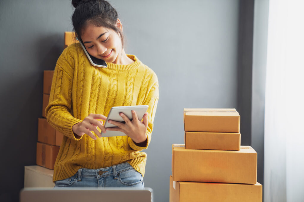 Image of young, happy Asian woman on her cell phone and tablet, surrounded with packages